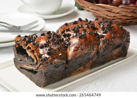 A loaf of chocolate babka with coffee in the background - stock photo