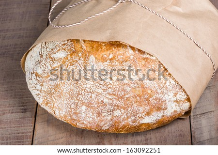 A loaf of fresh baked bread wrapped in paper - stock photo