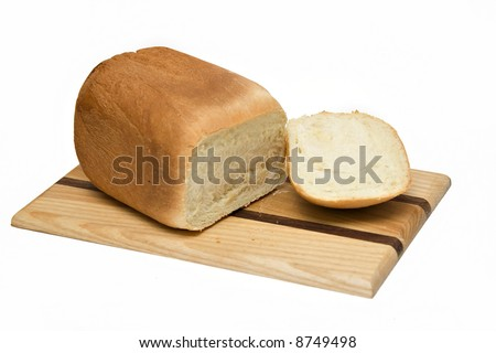 A loaf of homemade white bread - fresh from my bread machine!  Wooden cutting board; isolated on white.