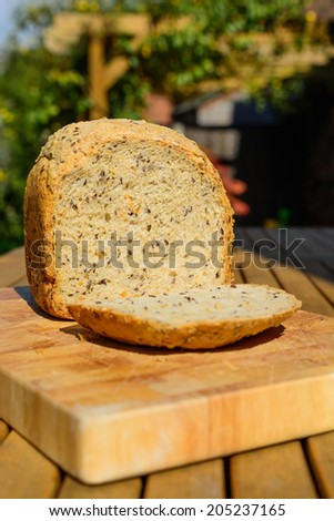 A loaf of wholemeal bread in the summer sun on a wooden chopping board - stock photo