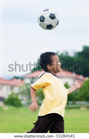 A Local boy playing football - stock photo