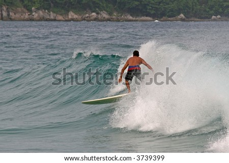 A local surfer rides a wave in Phuket, Thailand - stock photo
