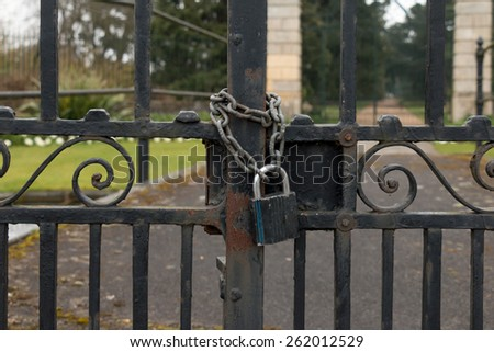 A Lock and Chain on Metal Fence Gate to the Road