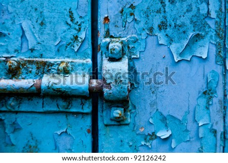 A lock on aged painted blue doors - stock photo