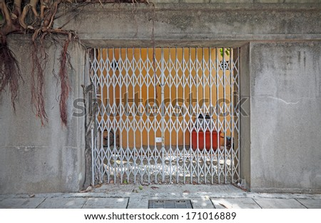 A locked metal sliding grille door with old stone mason frame.  - stock photo