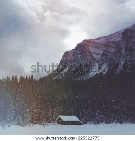 A log cabin situated at the bottom of a mountain in the snow. - stock photo