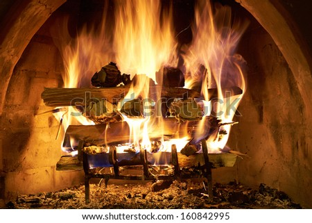 A log fire burning furiously in a stone fire place. - stock photo
