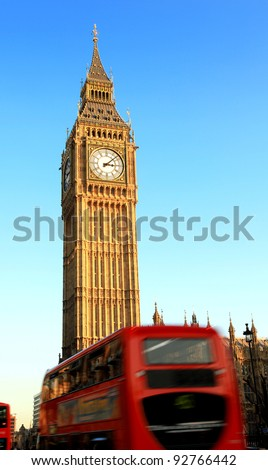 a london bus travels past big ben, with motion blur on the bus - stock photo