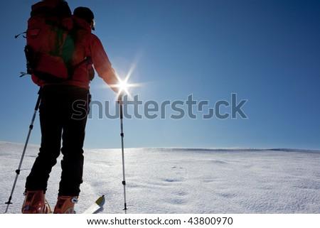A lone backcountry skier (ski touring), walks up to a snowed mountain ridge. - stock photo