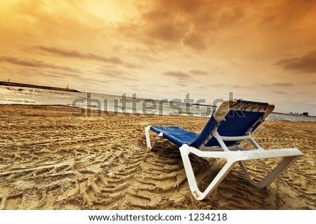 A lone beach chair at sunset