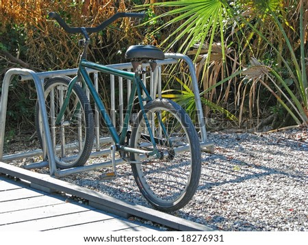 a lone bicycle parked in bike rack - stock photo