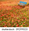 A lone, blue bench in a park surrounded by autumn leaves. - stock photo