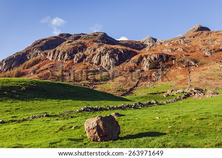 A lone boulder stands in a field in front of the imposing Langdale Pikes. - stock photo