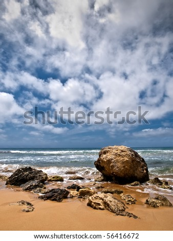 A lone boulder surrounded bu other fragments of rock on the edge of the coastline - stock photo