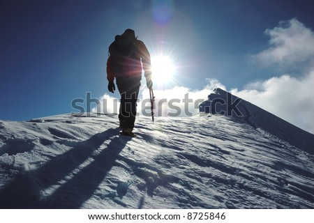 A lone climber reaching the summit of the mountain; back lite. West Alps, Swiss. - stock photo