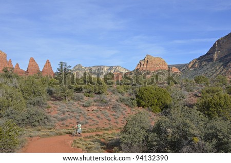 A lone cyclist on a stunning path under the imposing and majestic red rock cliffs of scenic Sedona, where mystery is palpable and the natural beauty, overwhelming. - stock photo
