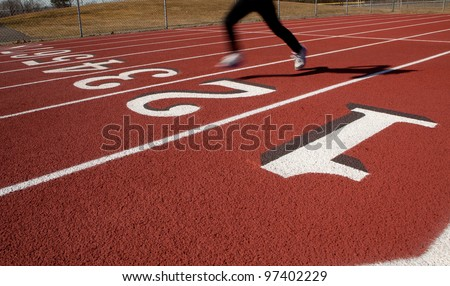 A lone female runner on a ruberized track at the start/finish line - stock photo