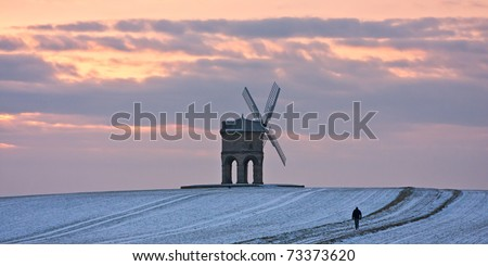 A lone figure walking in a snowy winter landscape at sunset at Chesterton windmill in Warwickshire, England. - stock photo