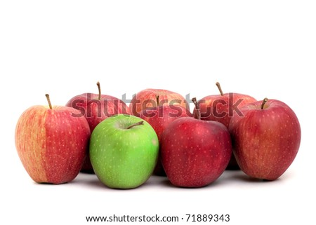 A lone green granny smith apple sits amongst a crowd of red delicious apples. - stock photo