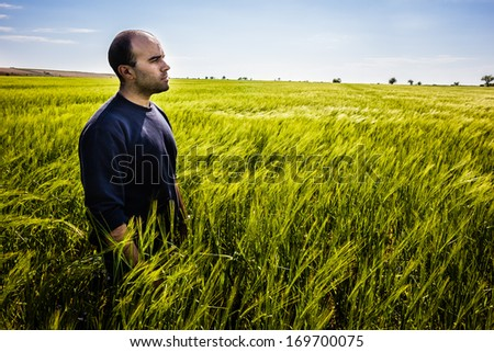 a lone man walking in a big green field