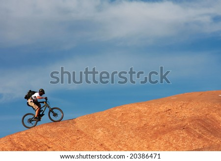 A lone mountain biker rides a steep section of Moab's famous slickrock mountain bike trail.