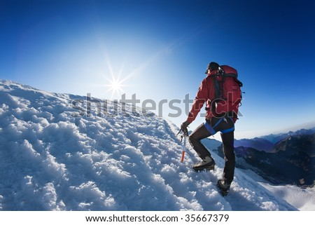 A lone mountaineer reach the top of a high mountain peak. Monte Rosa, Swiss. - stock photo