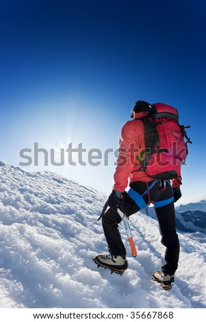 A lone mountaineer reaches the top of a high mountain peak. Monte Rosa, Swiss. - stock photo