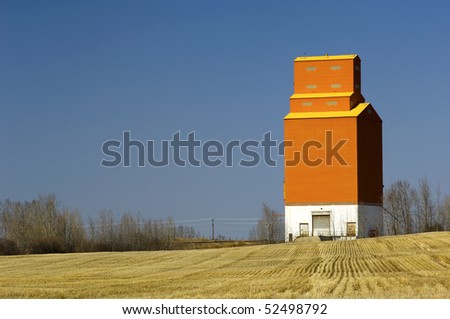 A lone, orange grain elevator stands at attention with grain stubble surrounding it.