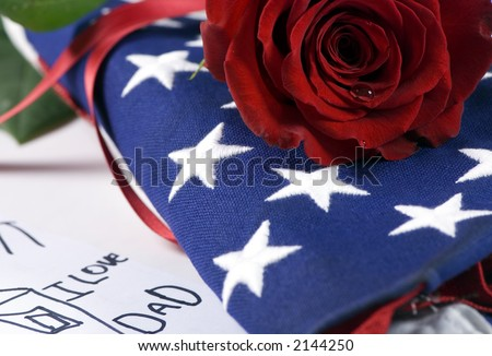 A lone red rose lying on top of a folded American flag. A single tear drop falls from the rose. I miss my daddy….my hero. - stock photo