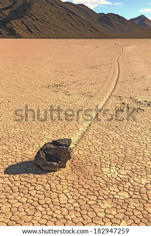 a lone rock racing down the playa in death valley - stock photo