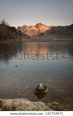 A lone rock stands defiant on the shore of Wast Water - stock photo