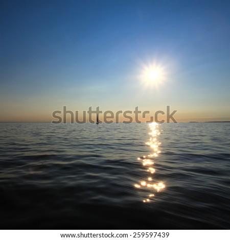 A lone sailboat in the sun - stock photo