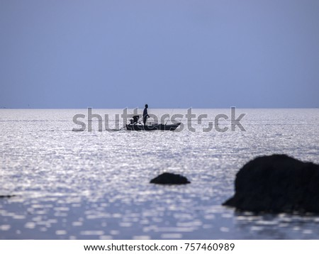 A lone, silhouetted fishing boat glides across the ocean near Ko Chang, Thailand