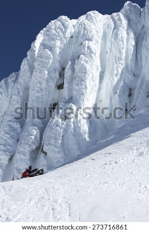 A lone snowmobile sits next to a tall glacier at the top of Mount Baker - stock photo