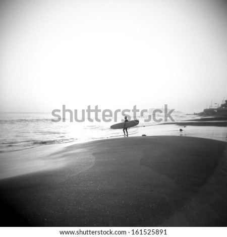 A lone surfer on the shore looking at the waves. - stock photo