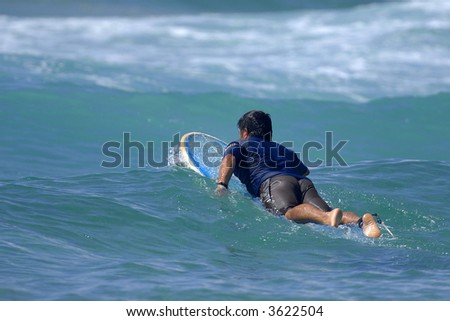 A lone surfer paddles out through the surf and waves. - stock photo