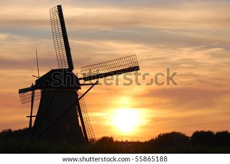 A lone windmill at sunset - stock photo