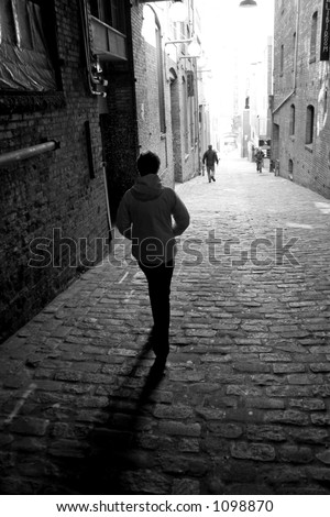 A lone woman is walking down a dark alley with two men in front of her in black and white. - stock photo