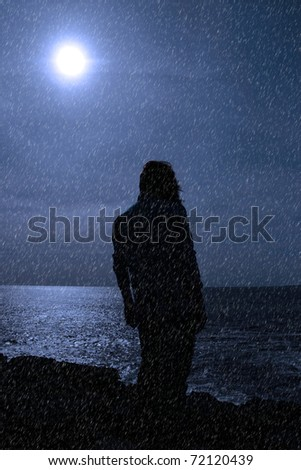 a lone woman looking sadly over the cliffs edge in county clare ireland during a rain storm