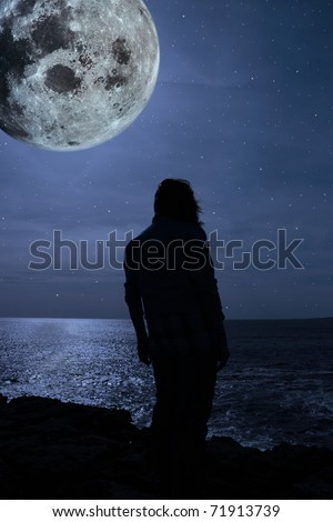 a lone woman looking sadly over the cliffs edge under the full moon in county clare ireland