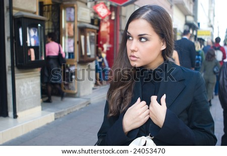 A lone woman walking down the street, window shoping.