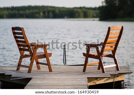 A lone wooden chairs sitting on the dock with a lake and cottages across - stock photo