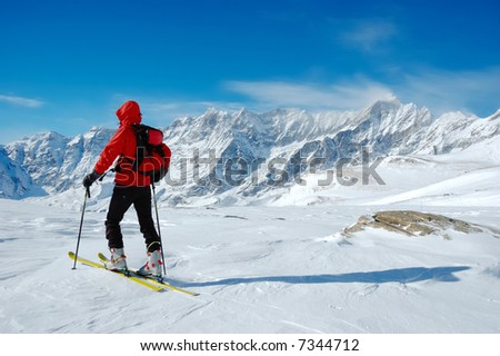 A lonely backcountry skier in a sunny winter day, alpine scenic, horizontal orientation