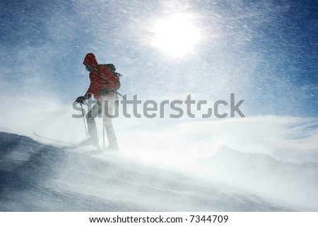 A lonely backcountry skier reaching the summit of the mountain during a snowstorm, horizontal orientation - stock photo
