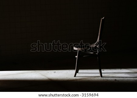 A lonely chair in a dark room immersed in a stray of bright day light