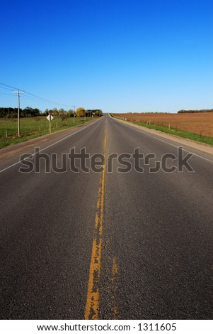 A lonely country road leading off into the distance. - stock photo