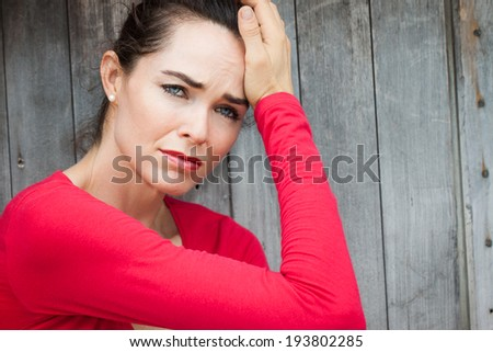 A lonely depressed and sad woman sitting by wall. - stock photo