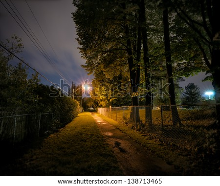 A lonely, deserted and spooky treed pathway at night time in a city park. - stock photo