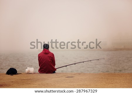 A lonely fisherman sitting and fishing at the dock. Image has a vintage effect. - stock photo