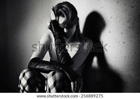 A lonely girl is sitting near a wall and hiding her face by a hand.